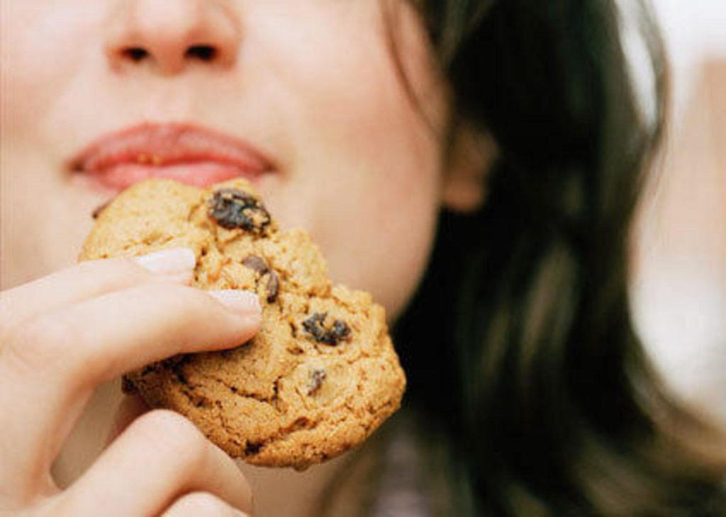 Девушка ест овсяное печенье с изюмом