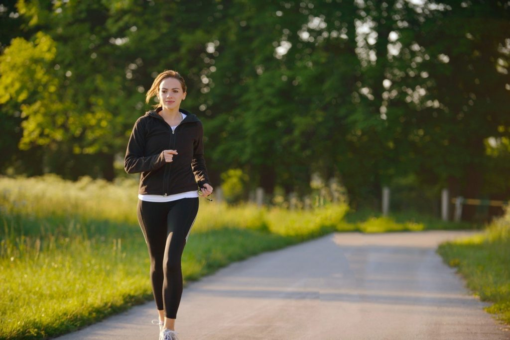 Девушка бежит по дороге на фоне леса