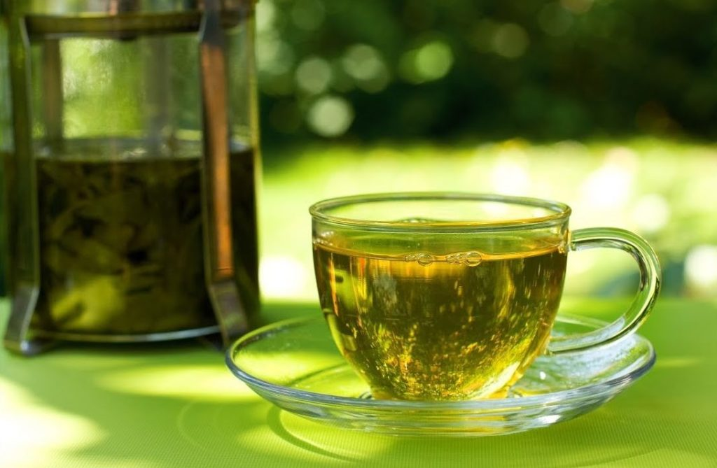 Зеленый чай в чашке и френч-прессе на зеленом фоне