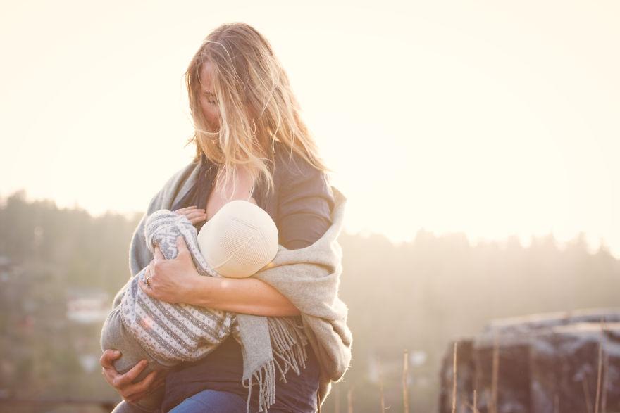 Девушка кормит грудью ребенка на улице