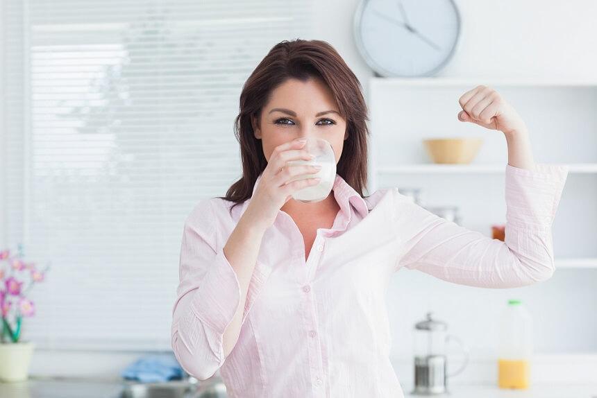 Девушка пьет из стакана смесь для мам и показывает бицепс