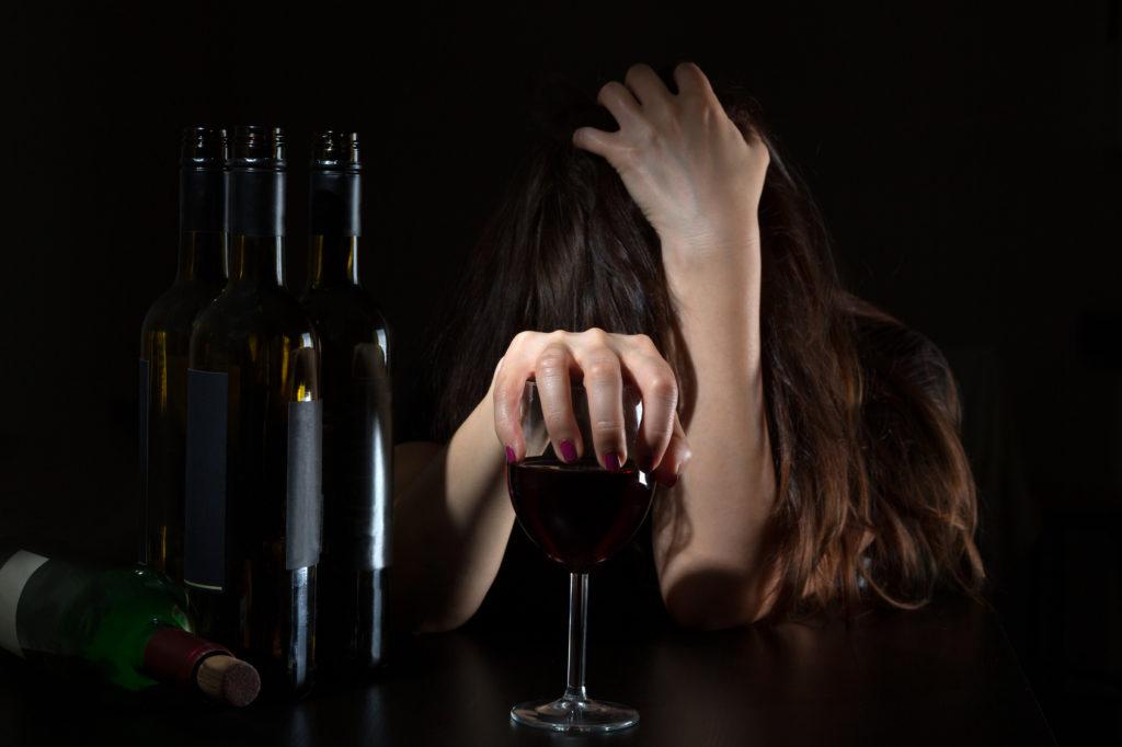Девушка держится за голову и за бокал вина, на столе перед ней стоят пустые бутылки из-под вина