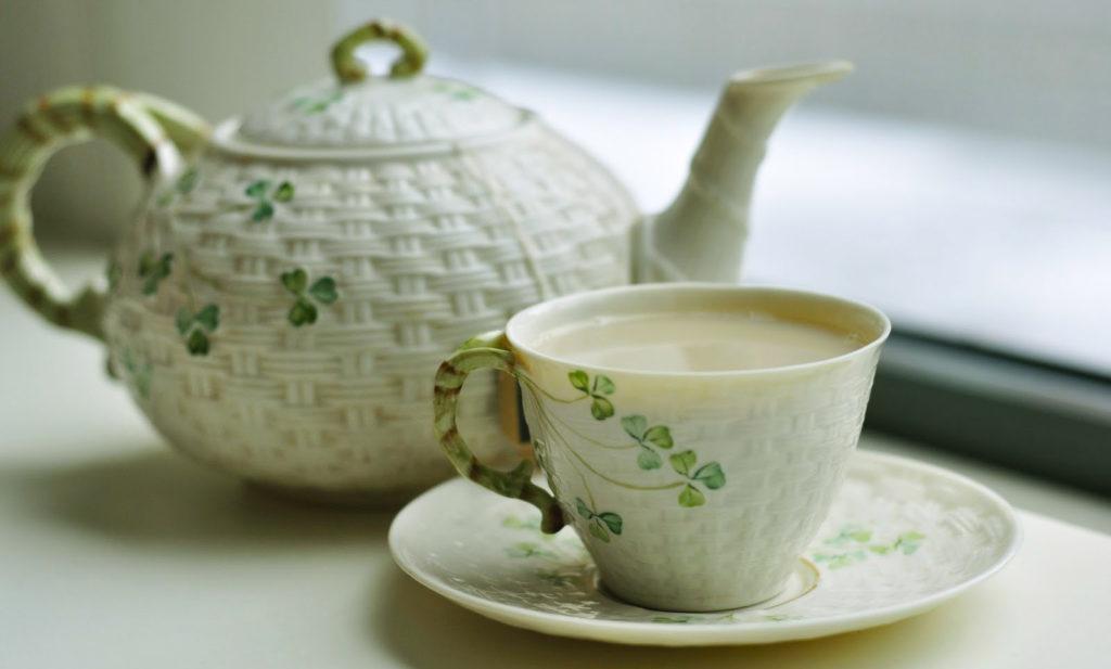 Зеленый чай с молоком в чашке на столе, заварочный чайник на заднем фоне