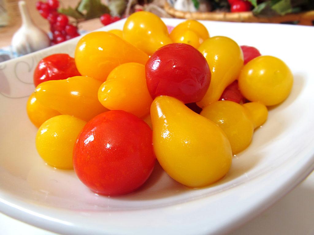Маринованные красные и желтые помидоры на белой тарелке