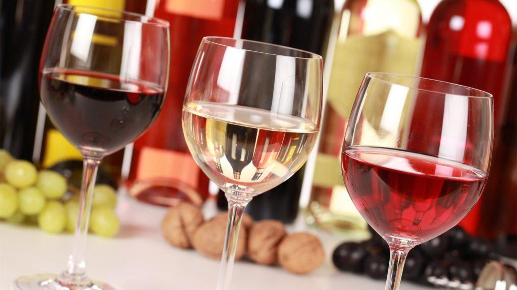 Три бокала вина на фоне бутылок