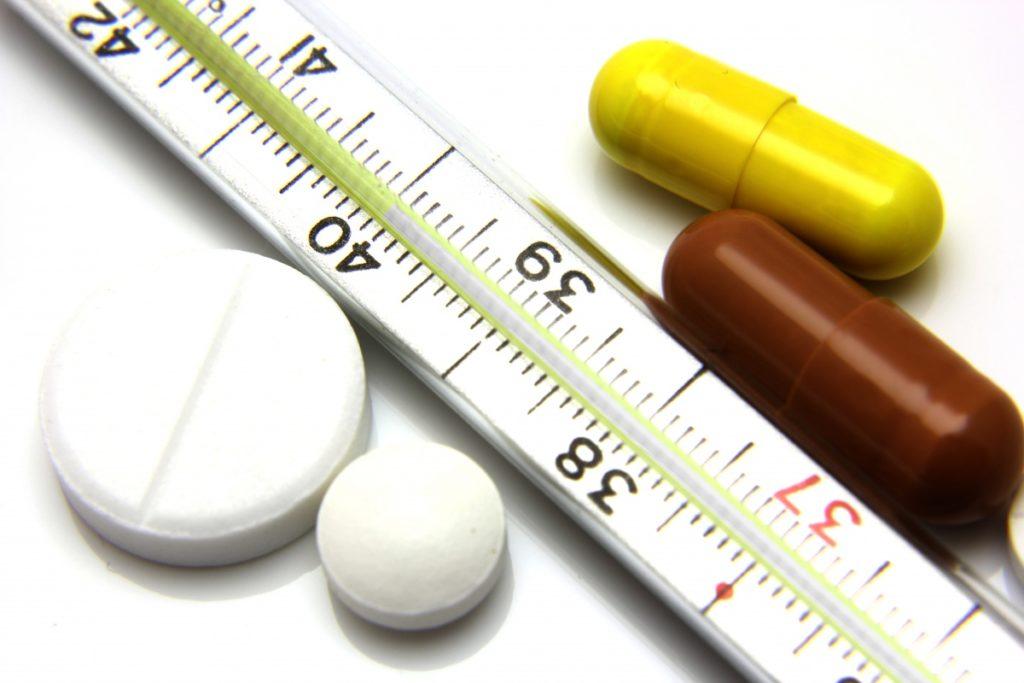 Термометр с высокой температурой, таблетки и капсулы на белом фоне