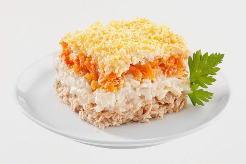Салат Мимоза на белой тарелке на белом фоне