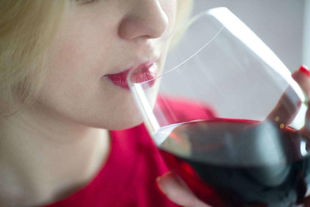 Девушка пьет красное вино из бокала