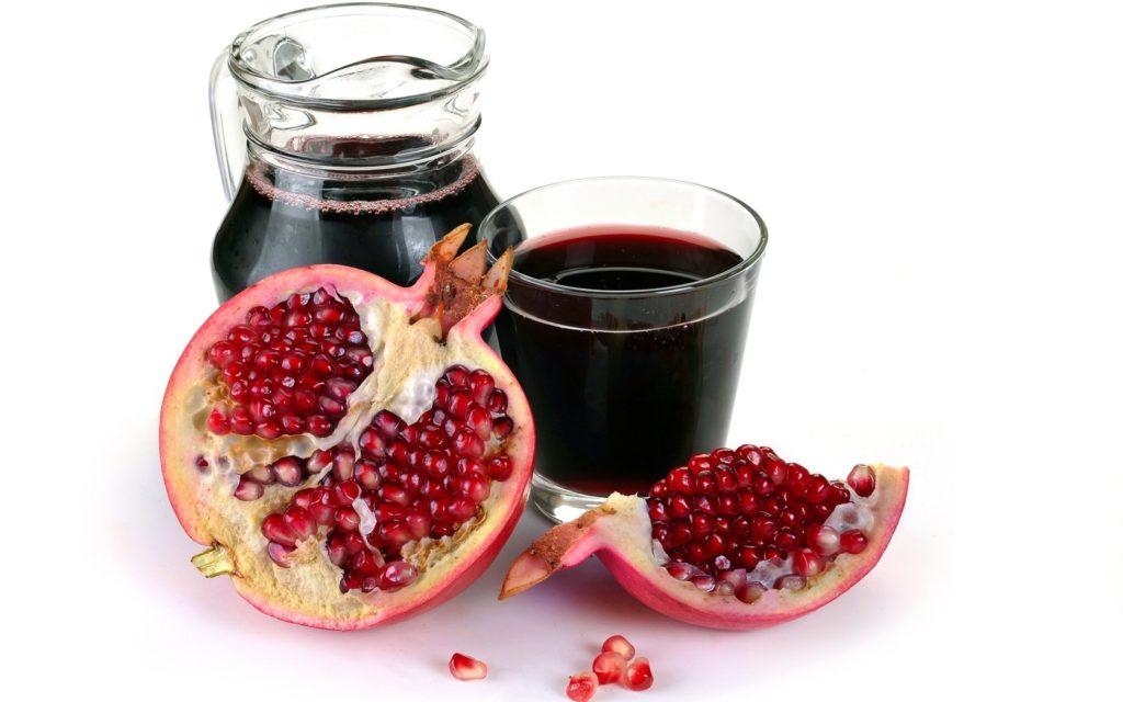 Гранатовый сок в стакане и графине и гранат на белом фоне