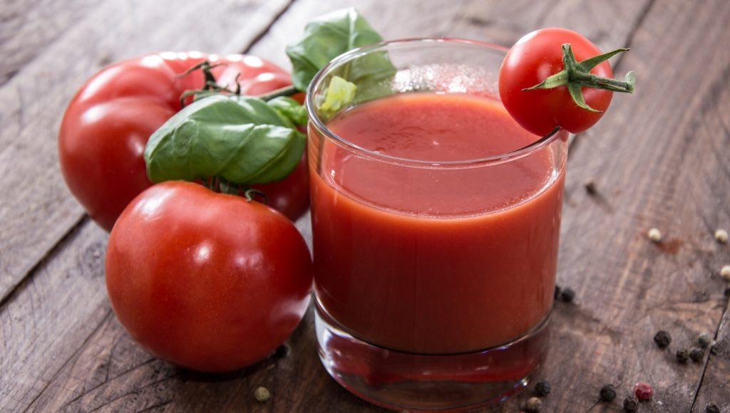 Томатный сок в стакане и помидоры на деревянном столе
