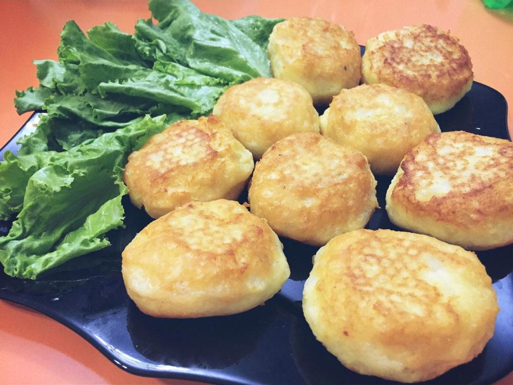 Картофельные оладьи на тарелке с листом салата