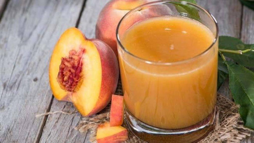 Персиковый сок в стакане и персики на деревянном столе
