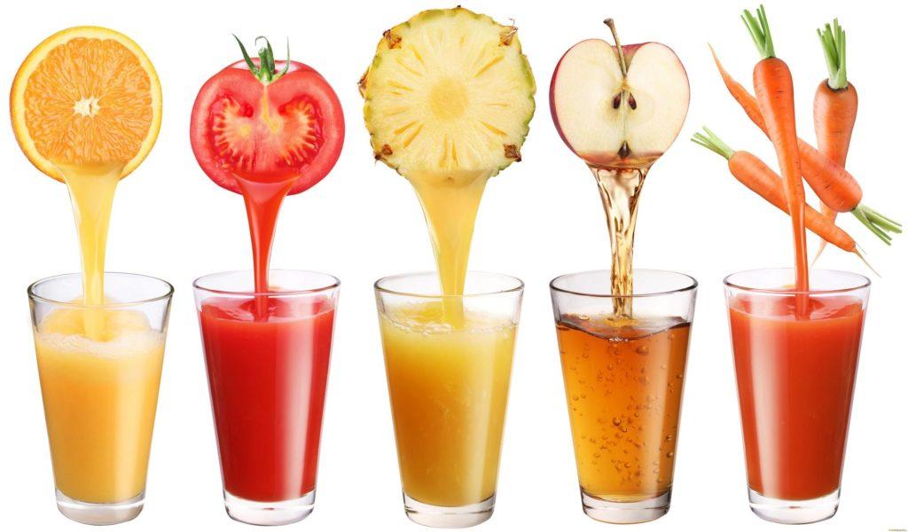 Стаканы с соком на белом фоне выдавливается сок из фруктов