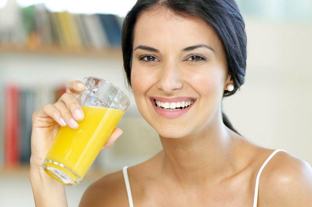 Девушка пьет апельсиновый сок из стакана