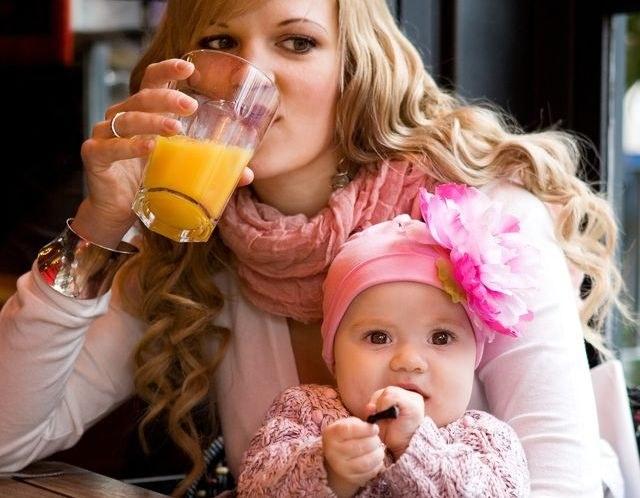 Женщина пьет сок из стакана с ребенком на руках