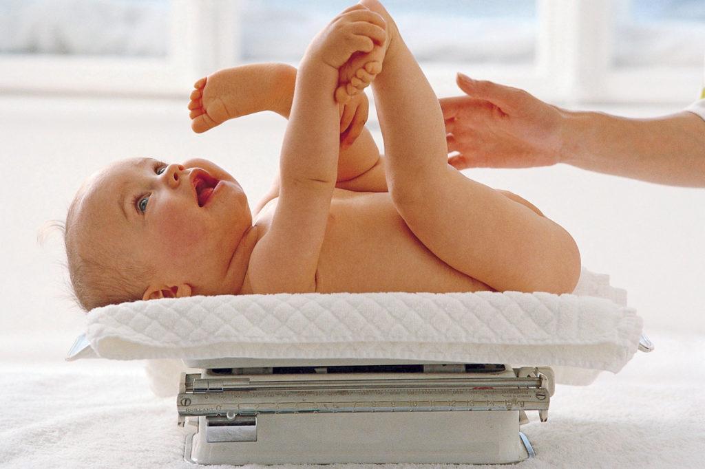 Ребенок лежит на весах