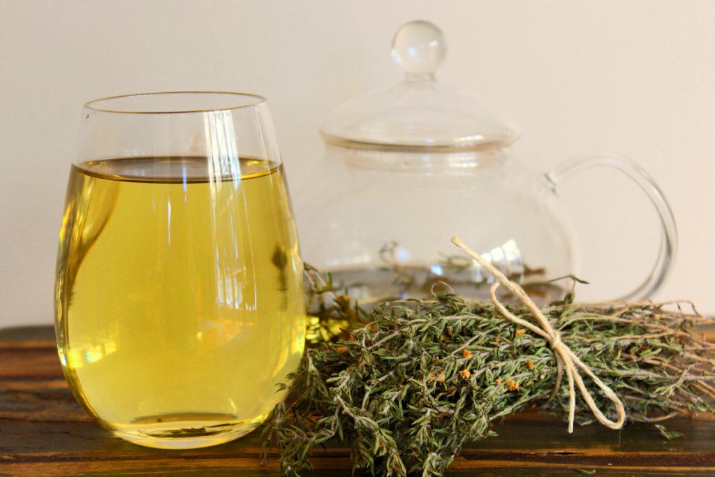 СТакан с чаем и сушеный чабрец на столе