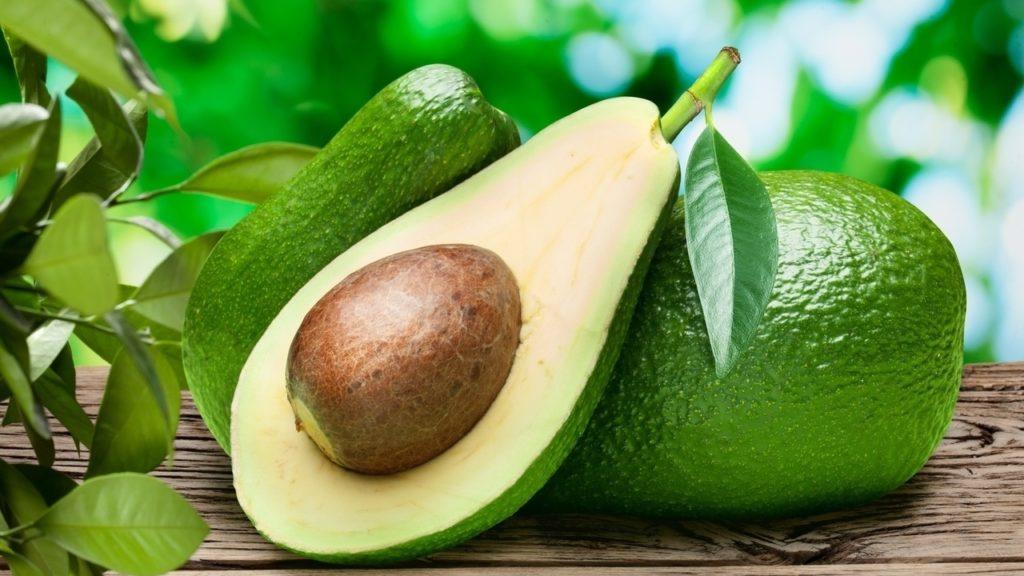 Авокадо лежит на деревянном столе два плода целых один в разрезе
