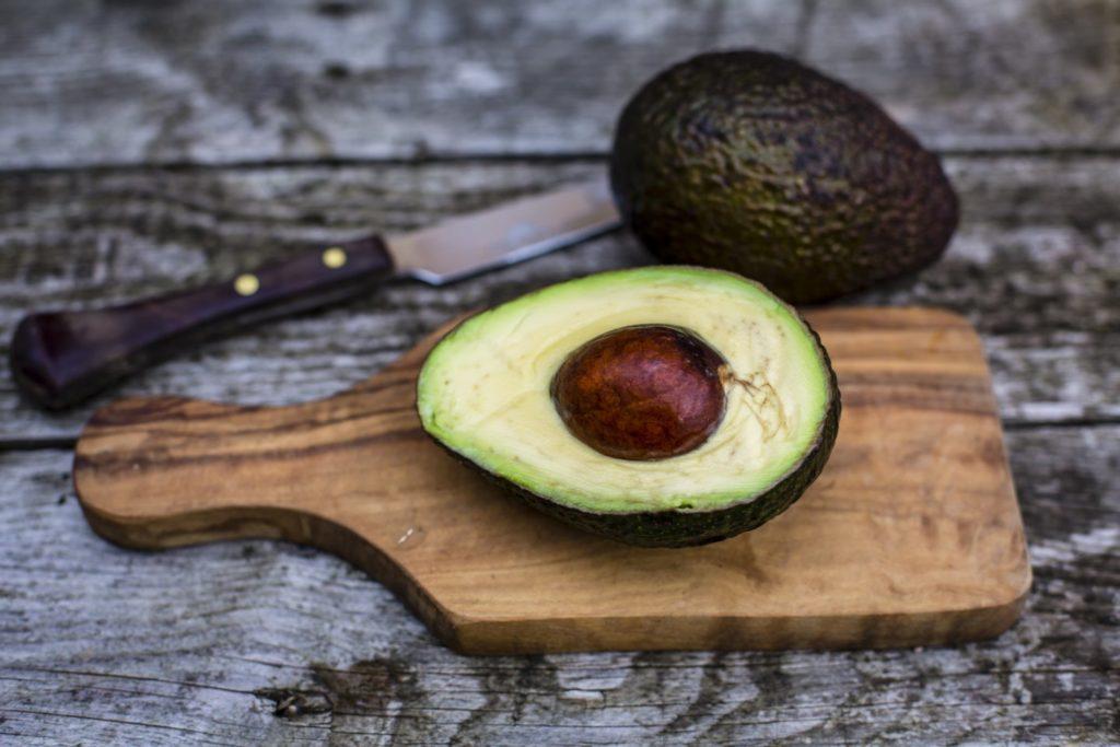 авокадо лежит на деревянной доске, рядом лежит нож