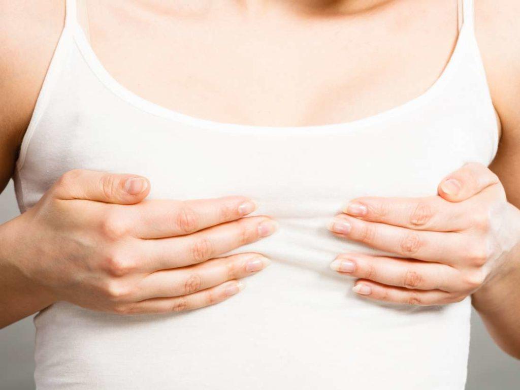 Женщина держится руками за грудь
