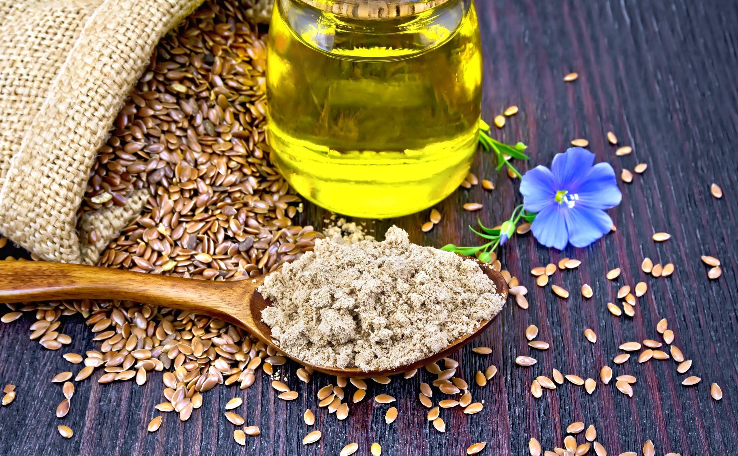 Семена льна в мешочке, льняное масло в стакане и льняная мука в ложке на деревянном столе