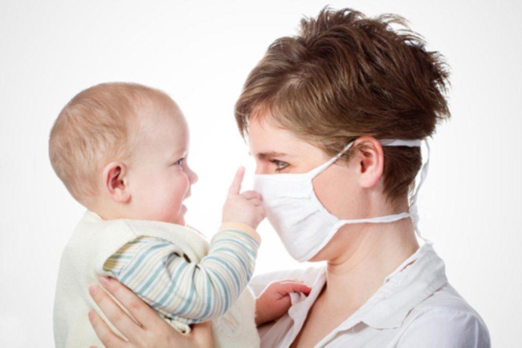 Женщина в медицинской маске держит ребенка на руках
