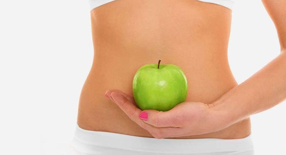 Девушка держит яблоко в руке перед животом