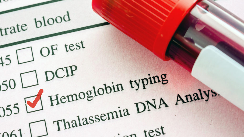 Красная отметка в бланке анализа на гемоглобин и образец крови в пробирке