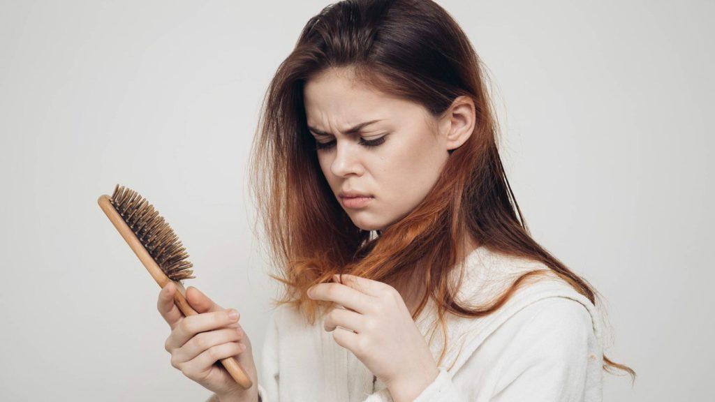 Женщина держит в руках расческу и смотрит на волосы