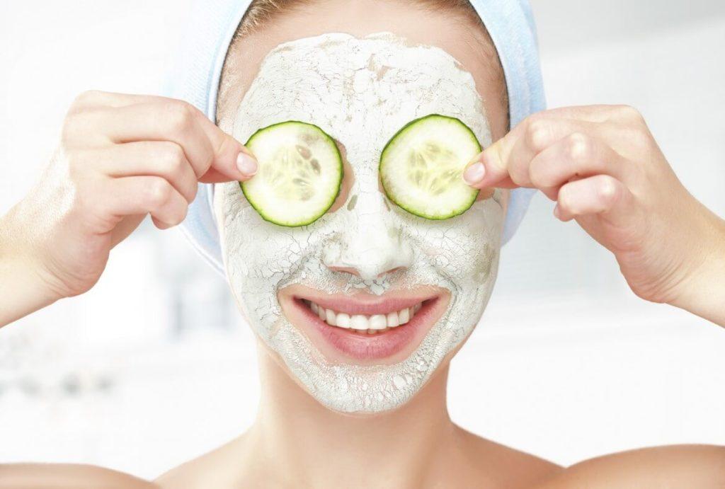Женщина с маской на лице и огурцами на глазах