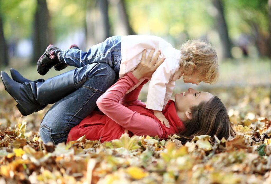 Женщина с ребенком лежат осенью на листьях