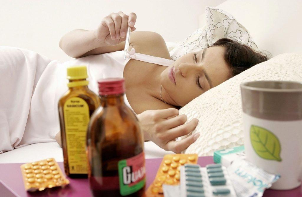 Женщина лежит в кровати и смотрит на градусник, перед ней стоят лекарства