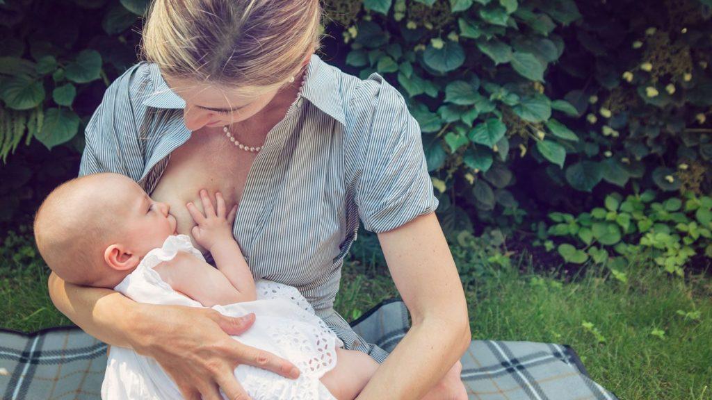 Женщина кормит грудью ребенка на улице