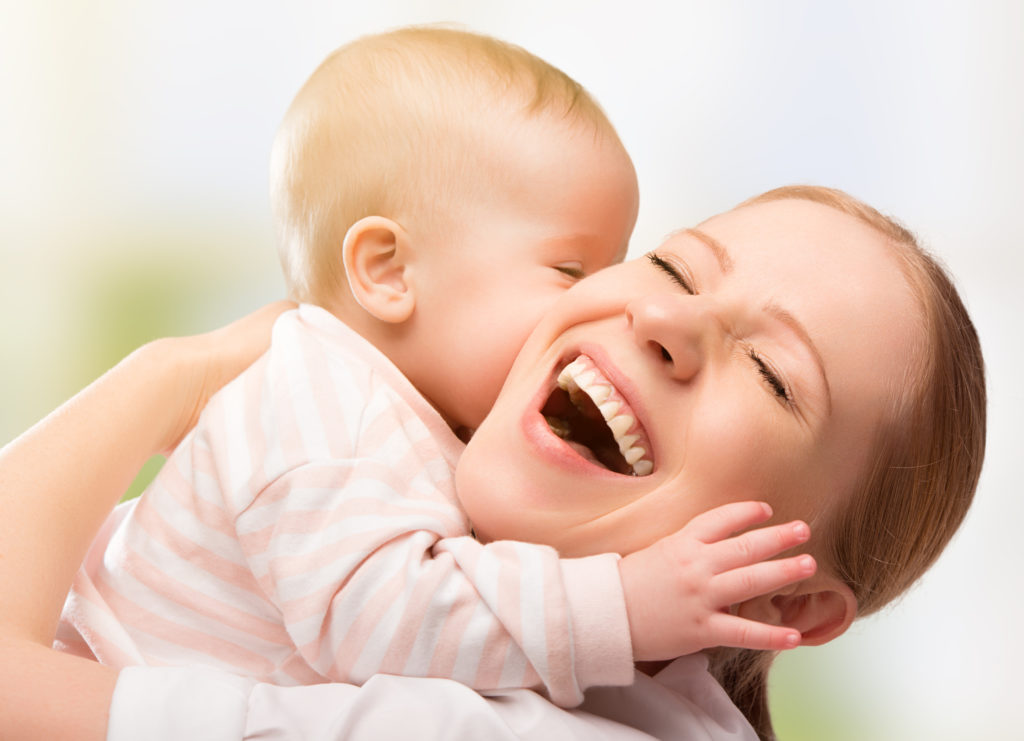 Женщина обнимает ребенка и смеется