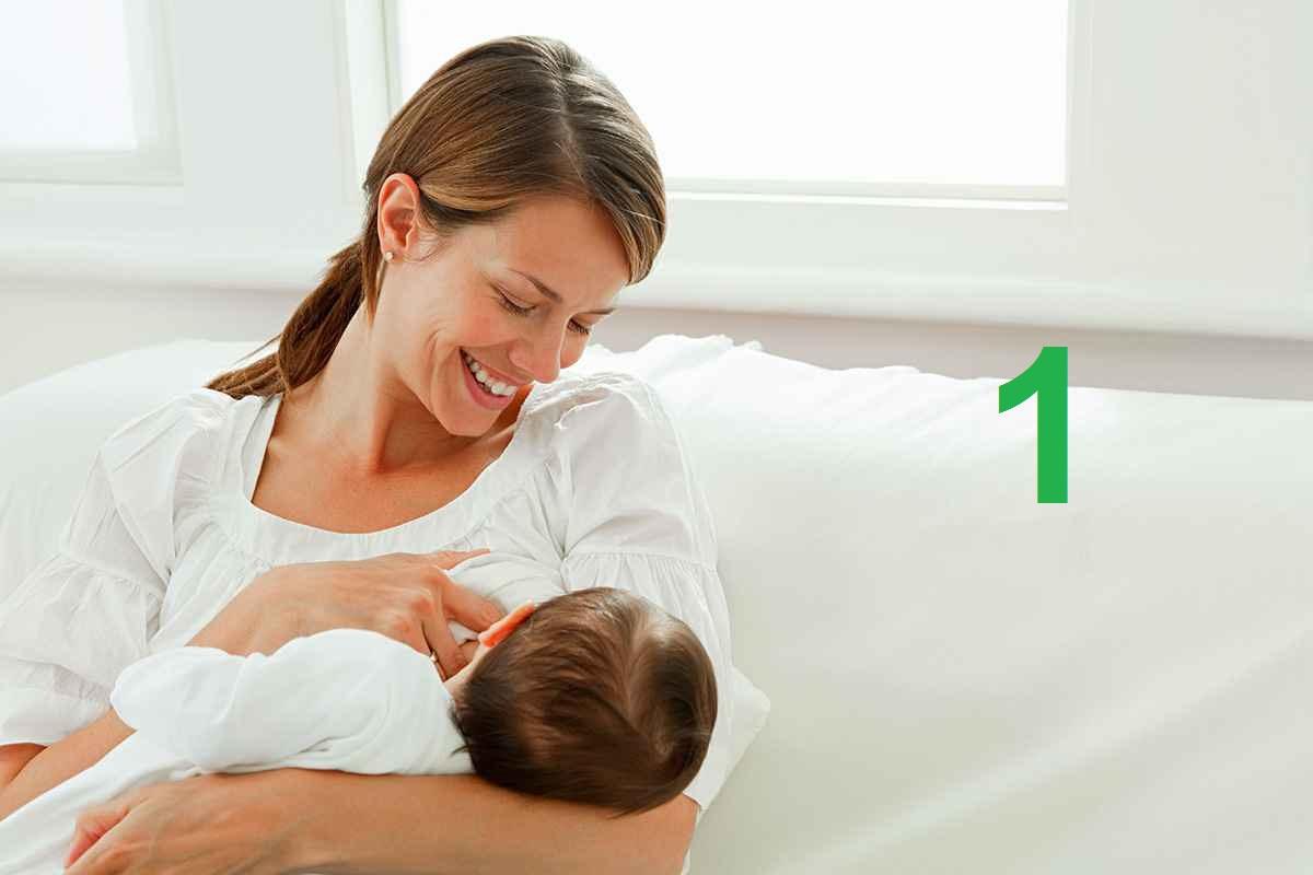 Женщина кормит ребенка грудью и улыбается