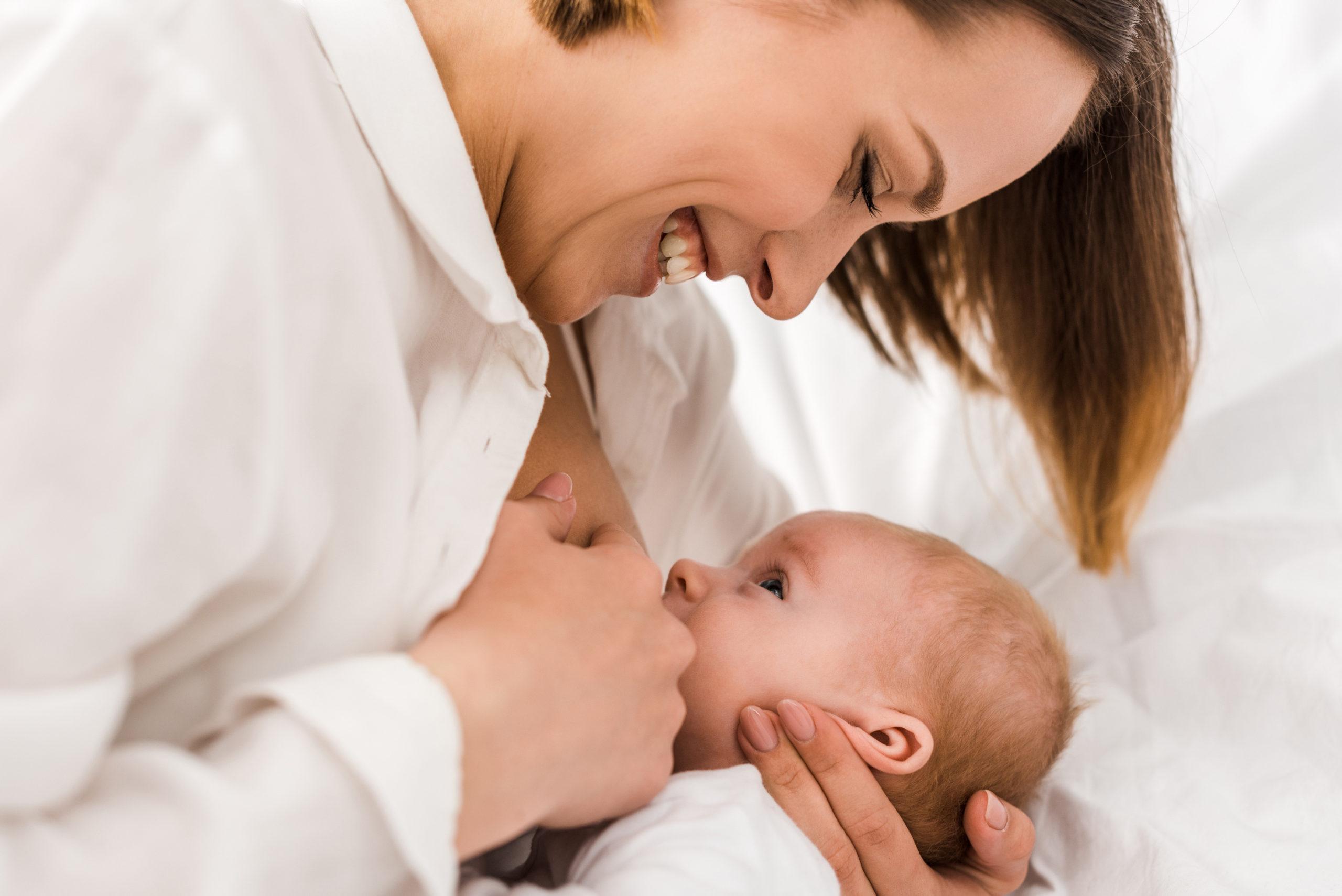 Молодая женщина улыбается и кормит ребенка грудью