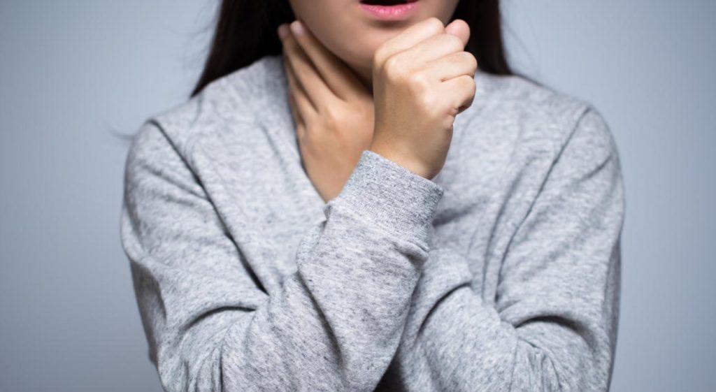 Женщина держится рукой за горло и кашляет