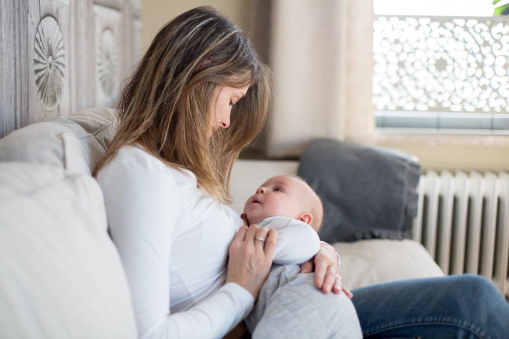 Женщина держит ребенка на руках, они смотрят друг на друга
