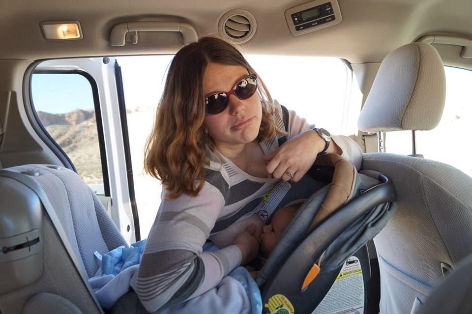 Женщина кормит ребенка в автокресле с нависанием