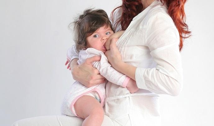 Женщина кормит ребенка грудью стоя, держа его на бедре
