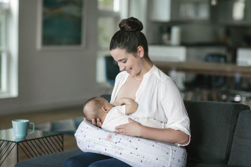 Женщина кормит ребенка грудью на подушке для гв