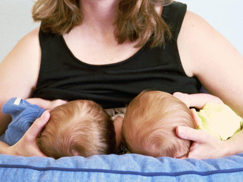 Женщина кормит грудью двоих детей одновременно