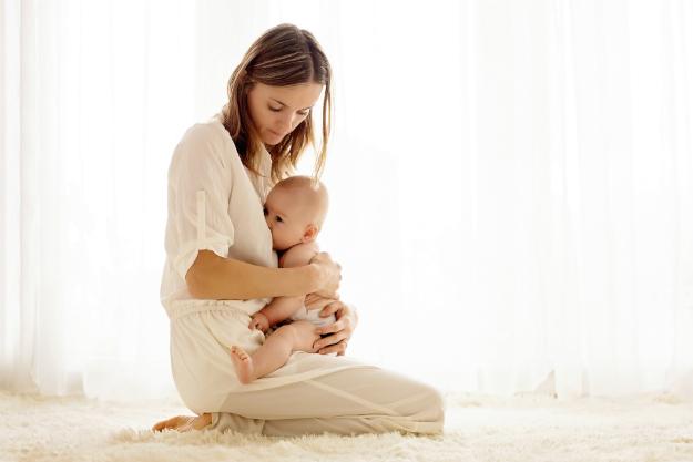 женщина кормит ребенка грудью сидя на коленях