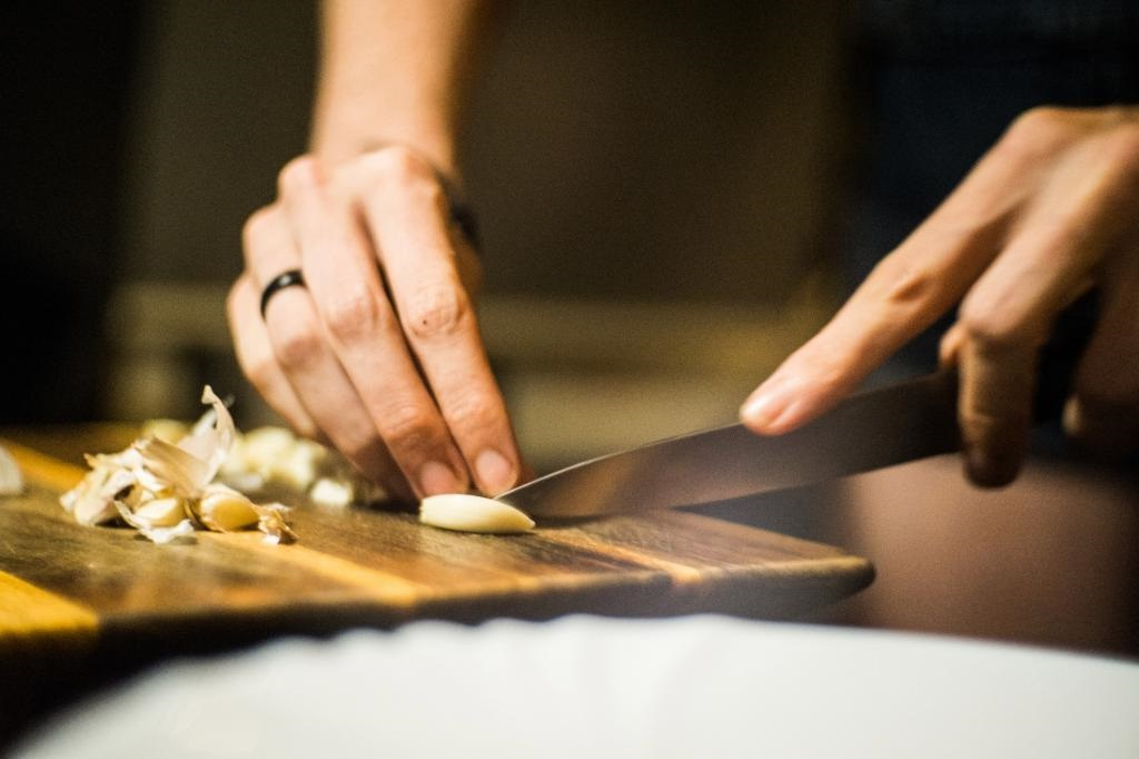 Женщина режет чеснок