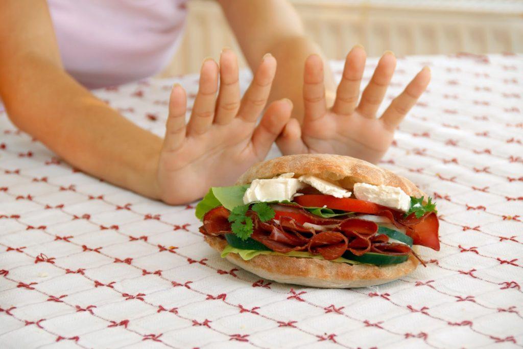 Аллергия на еду. Женщина отталкивает от себя бутерброд
