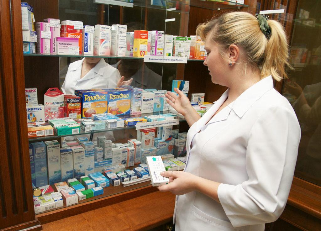 Женщина в белом халате перед витриной с лекарствами