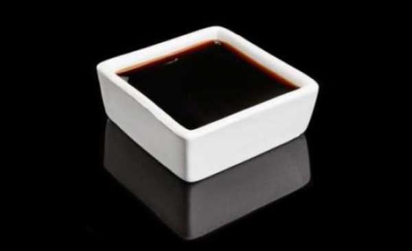 соевый соус в тарелке на черном фоне