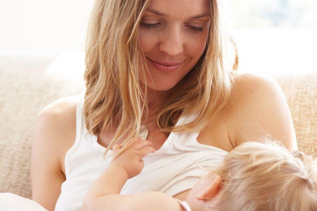 Женщина держит ребенка на руках и кормит грудью